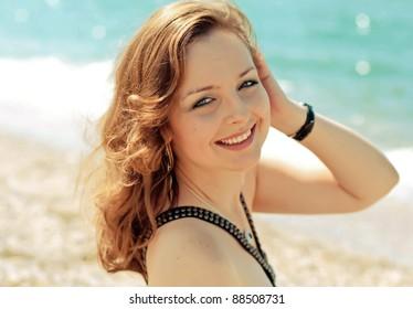 Pretty girl smiling near the sea, walking down the beach