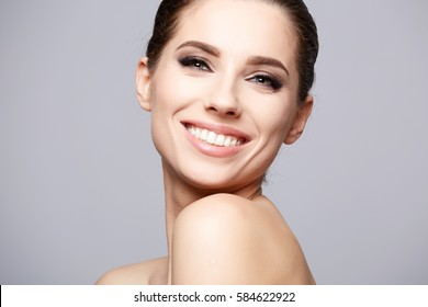 Pretty girl with smokey eye makeup, with naked shoulders, looking at camera and smiling, beauty photo, copy space, close up.