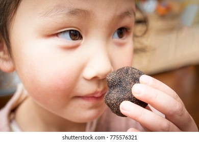 Pretty girl sniffing the truffle 's smell