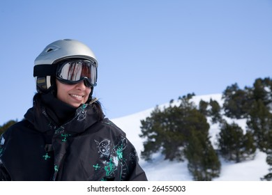 Pretty girl in snowboard clothes in helmet over blue sky
