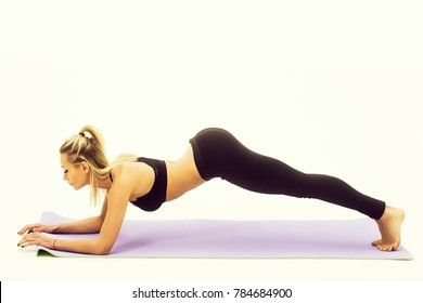 Pretty girl or sporty woman, fit athlete, with sexy, muscular torso, body, wearing black sportswear, bra, exercising on grey yoga mat isolated on white background. Fitness and healthy lifestyle