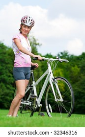 Pretty girl standing with a bicycle