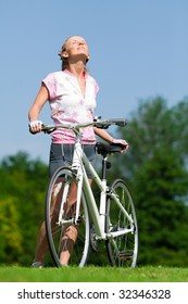 Pretty girl standing with a bicycle and enjoing the sun