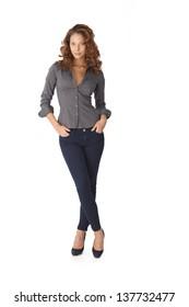 Pretty girl standing legs crossed over white background. Full length.