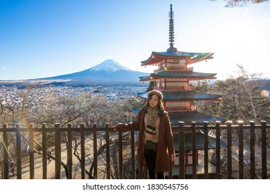Pretty Girl standing wich copy space at Beautiful view of mountain Fuji and Chureito pagoda, Fujiyoshida, Japan. Backgound of Fuji Autumn leaves during sunset with clear blue sky.