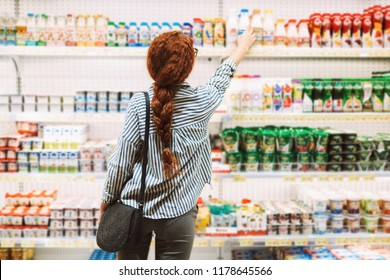 Pretty girl in striped shirt from back choosing dairy products in modern supermarket