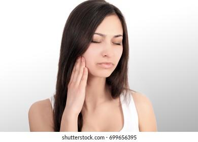 pretty girl with a strong headache on a grey backgroun