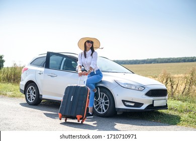 Pretty girl with suitcase standing near car and wiat for her dreaming trip