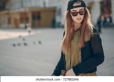 pretty girl in the summer city with smartphone