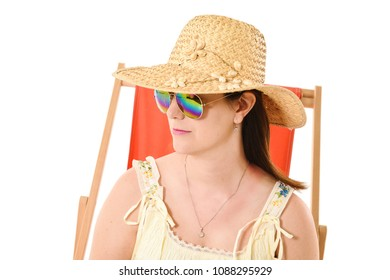 Pretty girl in sun hat and sun glasses sitting in orange deckchair and looking to one side. Taken in studio against white background. Space for text.