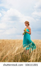 Pretty girl with sunflower in her hands walking through the wheat field