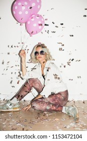 Pretty girl in sunglasses dreamily looking in camera with pink balloons in hand and confetti around over white background