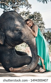 Pretty girl in sunglasses and green dress print kindly strokes elephant's trunk; exotic animals, glamour. Photo with noise