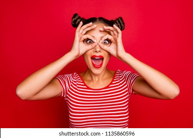 Pretty girl with surprised face holding fingers near eyes like glasses: mask like super hero or owl isolated on red background