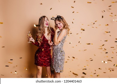 Pretty girl with surprised smile looking up during new year photoshoot with best friend. Wonderful ladies in party sparkle dresses enjoying champagne under confetti and laughing.