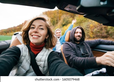 A pretty girl and taking selfie with group of friends during road trip in convertible car. Cheerful millennial students having fun when travel in Europe.