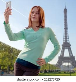 "Pretty girl taking a ""selfie"" in Paris, France on Eiffel Tower background"