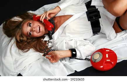 Pretty girl talking by red vintage phone.
