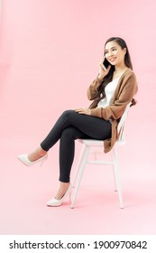 pretty girl talking on her cell phone sitting on a white chair