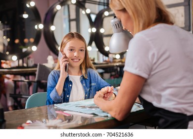 Pretty girl talking on the phone while having nails done