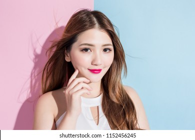 pretty girl that she is touching face with pleasure isolated on a pink and blue background.