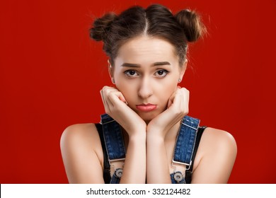 Pretty girl, with top knot hairdo, wearing on denim jumpsuit, posing with offended face expression, on the red background, in studio, waist up