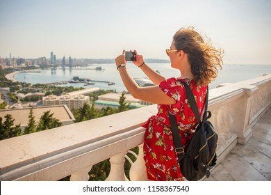 Pretty girl tourist taking photo of Baku city from the observation deck. Great vacation in Baku, Azerbaijan.