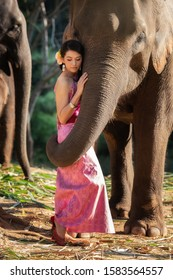 Pretty girl in traditional thai costumes in elephant's trunk hug with love.