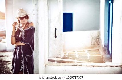 Pretty girl traveling to Greece, enjoying beautiful traditional architecture of Milos island, active summer holidays
