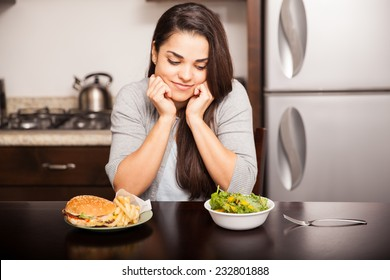 Pretty girl trying to decide between a healthy meal and a delicious one in the kitchen