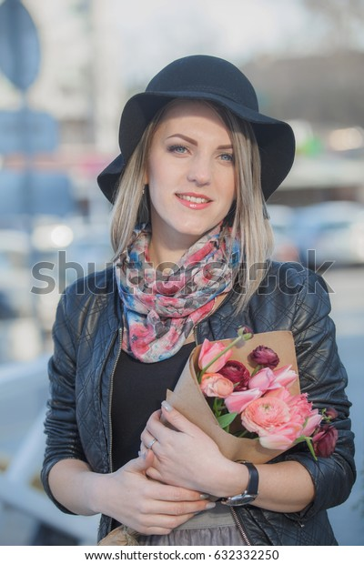 Pretty girl with tulips at a street