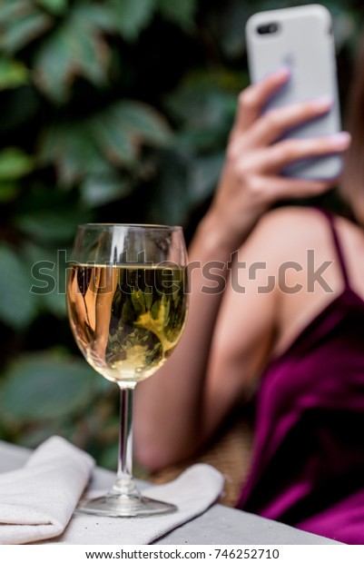Pretty girl uses phone in cafe with glass of wine