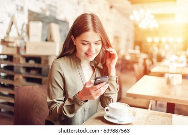 Pretty Girl Using Cell Phone Smiles.In caffe.With coffee and pizza.