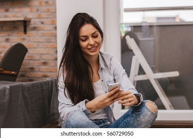 Pretty girl using her smartphone at home, reading messages, smiling