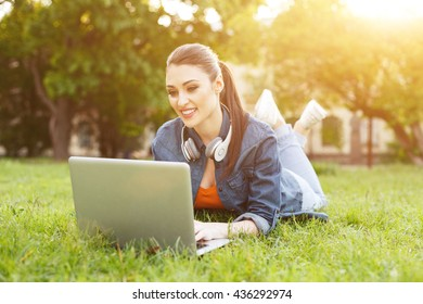 Pretty girl is using notebook in park