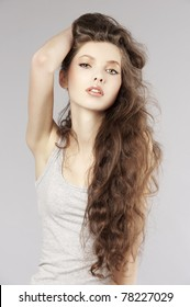 pretty girl with very long curly hair in a fashion portrait looking in camera