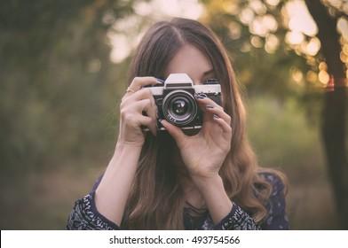 Chica guapa con cámara vintage en el parque