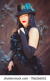 Pretty girl in a vintage style of 20s with feathers. The lady in a long black dress with bright make-up, pale skin near the European Catholic Church. Luxury retro look