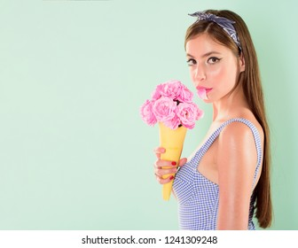 pretty girl in vintage style. pinup girl with fashion hair. flower bouquet. Florist. Summer. pin up woman with trendy makeup. retro woman eating ice cream from flowers, copy space. Carefree and happy.