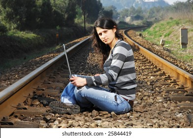 pretty girl waiting for the train on a railway with a laptop, computer