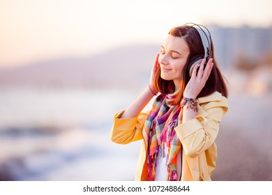Pretty girl is walking along the seashore at sunset and listening to music.