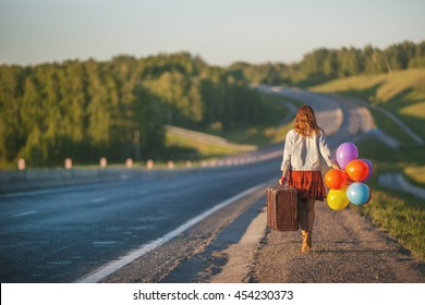Pretty girl walking with big suitcase and colored balloons on the road. Sunlight, sunset, wildflowers, spring. Enjoying freedom and travel