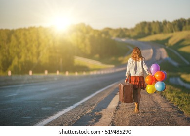 Pretty girl walking with big suitcase and colored balloons on field road. Sunlight, sunset, wildflowers, spring. Enjoying freedom and travel