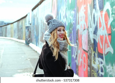 Pretty girl walking next to The Berlin Wall full with graffiti