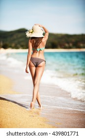 Pretty girl walking on a sand beach in a bikini and enjoying the sun