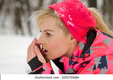 Pretty girl warm up hands while jogging on cold winter day in nature. Blonde woman warming hands with warm breath.Close up profile woman jogging in sports wear. Stylish girl in cold day outdoor.
