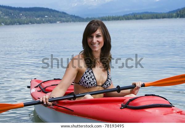 Pretty girl wearing a bikini and sitting in a kayak on a lake.