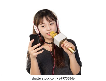 Pretty girl wearing a headset while singing with a wireless microphone and holding a phone