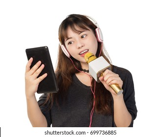Pretty girl wearing a headset while singing with a wireless microphone and holding a tablet computer