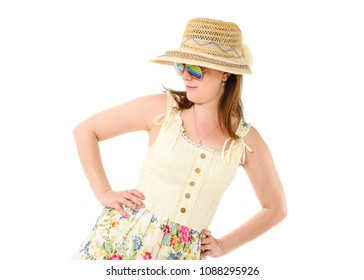 Pretty girl wearing a lemon-colored dress and sun hat and sun glasses looking downwards and with hands on hips. Taken in studio against white background. Space for text.